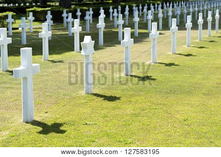 Historical american cemetery for dead soldiers of WWII with white cross and grass in Italy, near Anzio