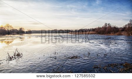 icy lake at sunset on cold winter