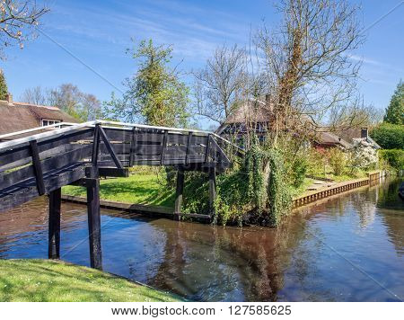 Bridge over canal in Giethoorn, a small village in the Netherlands. Part of the village has no car roads and some houses are accessible by boat only.