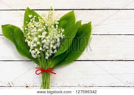 bouquet of lilies of the valley flowers with green leaves tied with a red rope in the water droplets on the white wooden boards. with space for posting information