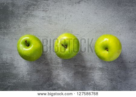 Three Green Apples On Concrete Background