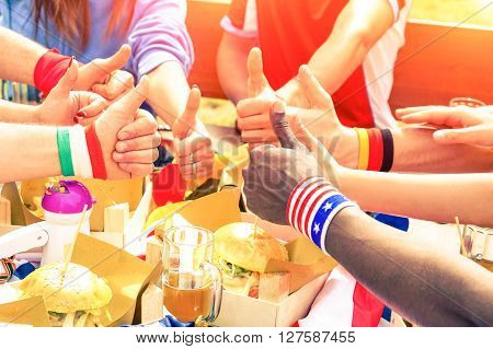 Multiracial group of friends thumbs up wear world flags cuffs - International sport fans hands circle and fun moment eating in cafe bar restaurant - Friendship joy peace concept - Focus on black hand
