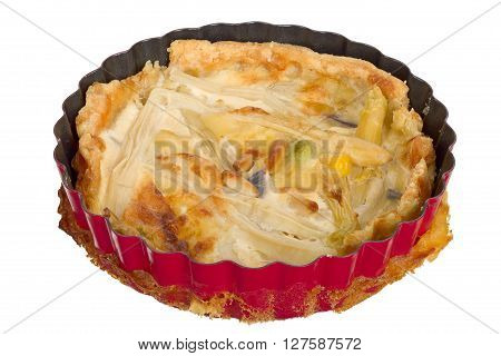 Handmade quiche in a small baking dish isolated on white background.