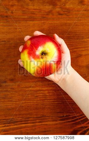Child Holding A Red Apple On Wooden Background. Top View