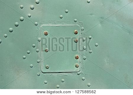 old iron plate with rivets hatch green paint