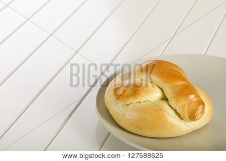 Bread roll on ceramic plate white wooden background.