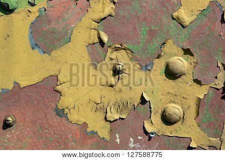 rusty plate with pieces of paint in the cracks and rivets