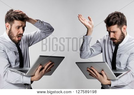 The young confused and frustrated man with his laptop computer on gray background