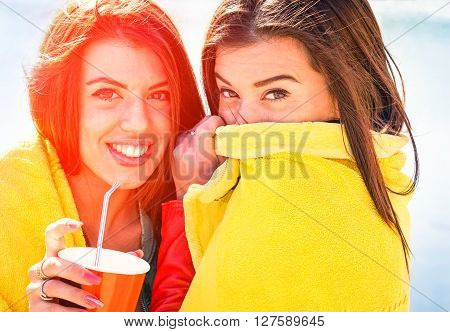 Best friend girls playful moment hiding face and looking camera - Beautiful girlfriends having fun on beach - Concept of summer holiday friendship and joy - Sun halo effect focus on right woman eyes