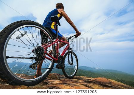 Young man standing with bicycle on top of a mountain