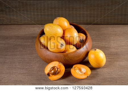 loquats in a wooden plate on a wooden background