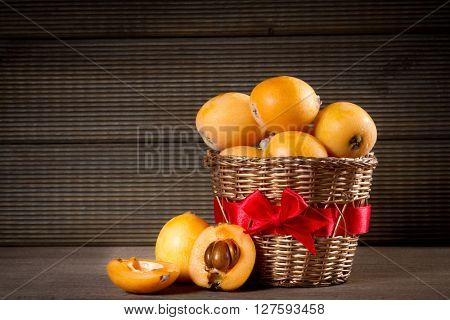 loquats in basket on wooden background