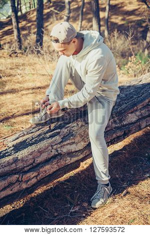 Sporty young man sitting on fallen tree trunk and tying shoelaces in the forest in summer