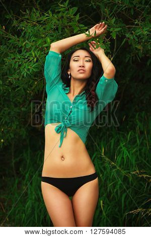 Sexy asian girl in pants and blouse outdoors