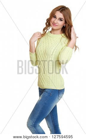 young girl casual dressed jeans and a green sweater posing in studio on white background