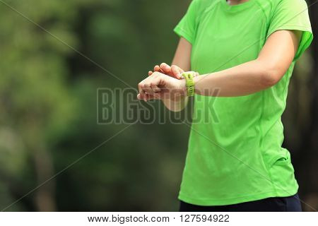 young woman jogger ready to run set and looking at sports smart watch checking performance or heart rate pulse trace.