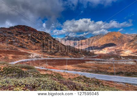 Beautiful curvy road passing through Jelepla Pass Dzuluk Sikkim India -with blue sky and clouds in the background