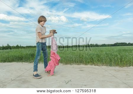 Sibling brother is supporting his younger sister doing handstand on farm field dirt road