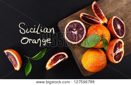 red blood oranges with cut and green leaves on a wooden board. Black background