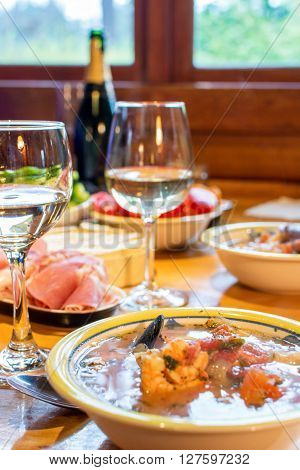 Italian dinner with seafood soup sliced prosciutto white wine and vegetables.