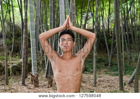 muscular young man doing yoga exercise over forest,