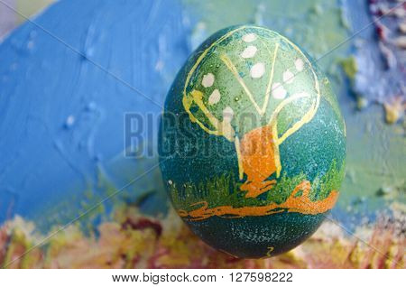 Single easter egg with beautiful color abstract picture isolated on colored textured background. Children painting.
