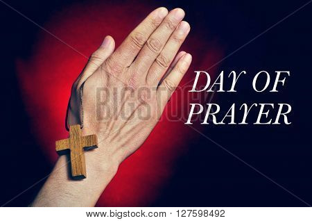 Man praying with a wooden cross in his hands and the text day of prayer