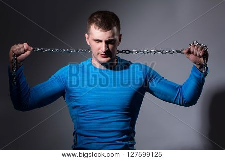 Young man with a tight chain in a blue shirt on a gray background