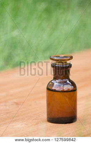 little brown bottle on wooden board and grass