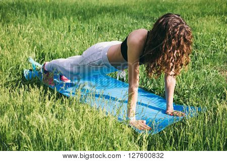 Curly Slim Woman Doing Exercises On The Green Meadow On The Mat