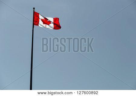 Canadian Flag Waving Over Pale Blue Sky