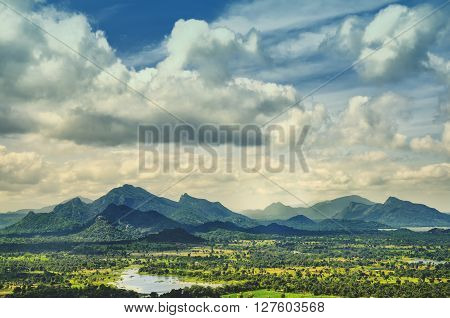 Green landscape with a hill overgrown with trees and blue sky on Sri Lanka. Sigiriya Lion Rock Sri Lanka.