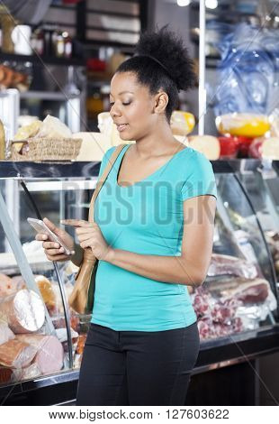 Customer Using Cell Phone In Grocery Shop