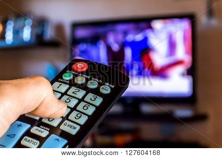 Hand hold the remote control to change channels on Tv