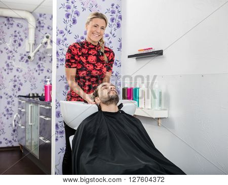 Confident Beautician Washing Male Customer's Hair