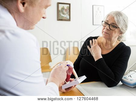 Woman Looking At Male Doctor Explaining Shoulder Rotator Cuff Mo