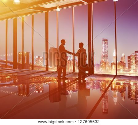 Silhouette of Business People Hand Shaking in the Office