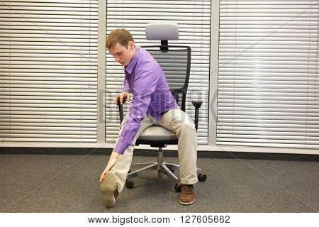 man exercising on chair in office,touching his foot, healthy lifestyle - front