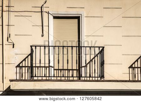 Fragment of a facade with closed shutters behind a balcony railing