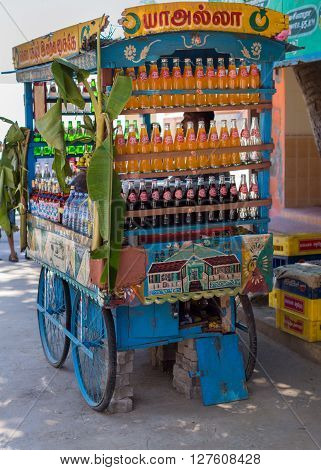 Thanjavur India - October 14 2013: Street vendor sells lemonade soda and water out of a simple blue puchcart. Banana leaves for Durga fest.