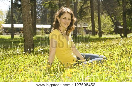 Young European woman with brown hair sit on meadow with yellow dandelions.