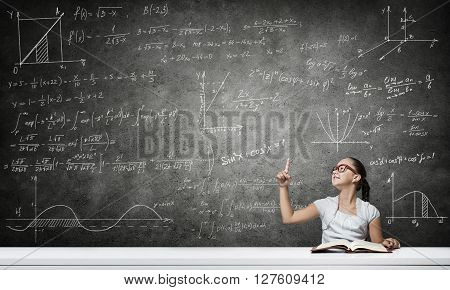 School girl in red glasses sitting at table pointing with finger up