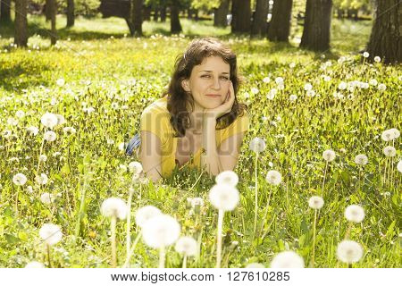 Young woman lies on meadow with white dandelions