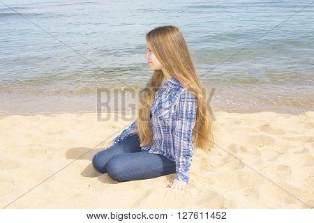 Young beautiful girl European long hair sitting on sandy beach near sea in profile.