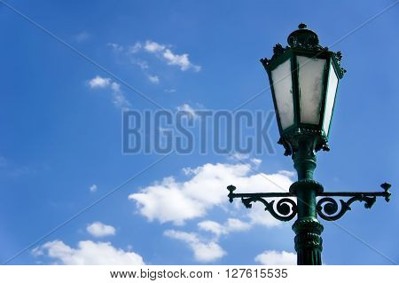 green street lamp post on blue sky background