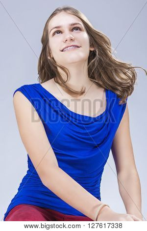 Caucasian Female Teenage Girl With Teeth Brackets in Studio. Sitting and Smiling. Vertical Image