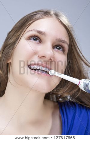 Dental Concept and Ideas. Closeup Portrait of Caucasian Teenage Girl Brushing Teeth Brackets with Electric Toothbrush.Vertical Image
