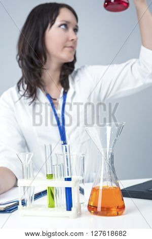 Female Caucasian Laboratory Staff Researching Liquids in Lab Glassware. Vertical Image Composition