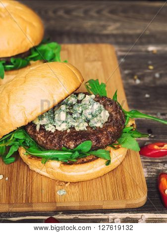 Fresh burger with blue cheese and arugula on rustic wooden background