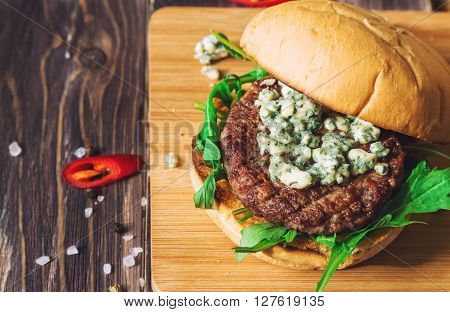 Fresh burger with blue cheese and arugula on rustic wooden background. Top View.